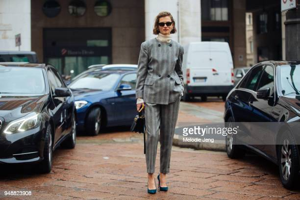 Model Giedre Dukauskaite wears a matching gray doublebutton plaid suit over a tan turtleneck with blue heels and a black purse during Milan Fashion...