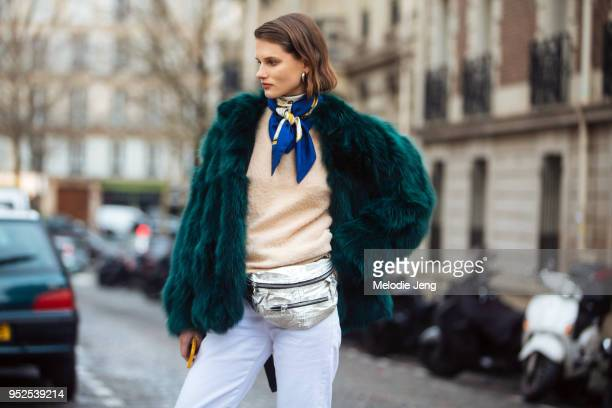 Model Giedre Dukauskaite wears a silver earring short green fur coat a blue scarf around her neck a cream sweater silver fanny pack and white pants...