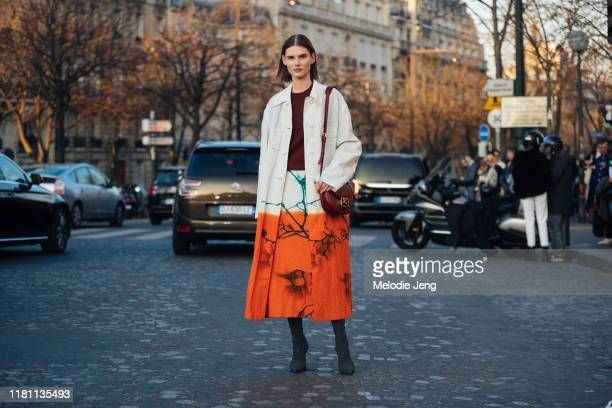 Model Giedre Dukauskaite wears a tan and orange Dries Van Noten coat and red Etro purse after the Rochas show during Paris Fashion Week Fall/Winter...