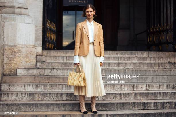 Model Giedre Dukauskaite wears a tan leather blazer, white skirt, a beige pleated skirt, a yellow Celine python medium clasp tote, and Chanel glitter...