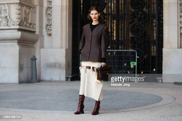 Model Giedre Dukauskaite wears a tweed brown blazer white knotted skirt Louis Vuitton by Virgil Abloh bag and brown boots after the Poiret show...