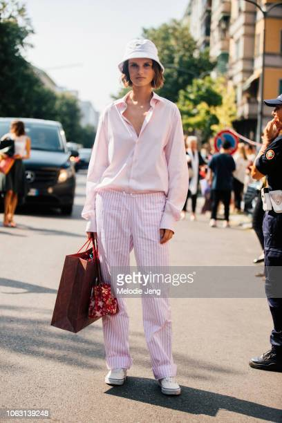 Model Giedre Dukauskaite wears a white Lacoste bucket hat light pink buttonup shirt light pink striped linen pants a red print bag and white Vans...