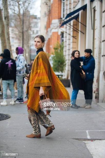Model Giedre Dukauskaite wears an orange cape, small brown boxy bag, python print pants, and brown boots after the Acne Studios show during Paris...