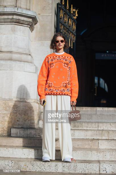 Model Giedre Dukauskaite wears an orange knit print Supreme sweater orange sunglasses Gabriela Hearst bag white pants and white OffWhite sneakers...