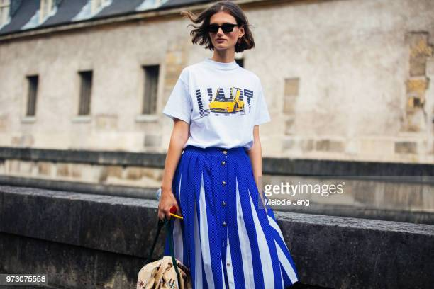 Model Giedre Dukauskaite wears black rectangular sunglasses a KAR / L'Art de L'automobile car tshirt white and blue pleated skirt during Paris...
