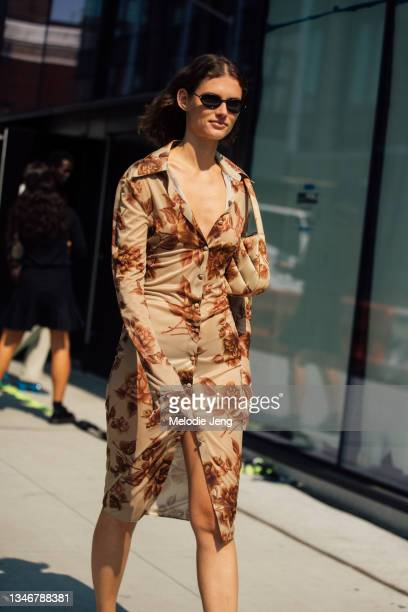 Model Giedre Dukauskaite wears black sunglasses, a matching light brown floral dress and purse after the Khaite show on September 12, 2021 in New...