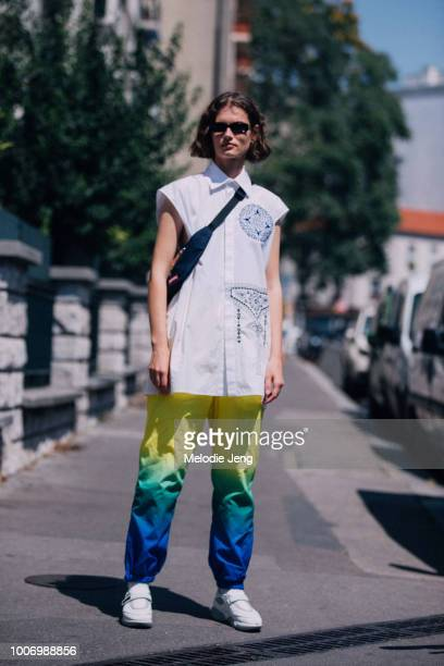 Model Giedre Dukauskaite wears black sunglasses a white sleeveless long shirt rainbow paints and white Prada cloudburst sneakers during Couture...