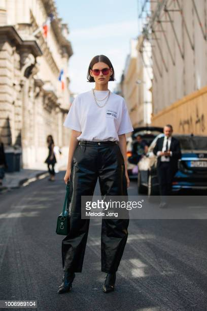Model Giedre Dukauskaite wears Dior pink sunglasses a L'Arte De L'automobile tshirt OffWhite green bag loose black Celine trousers and black heels...