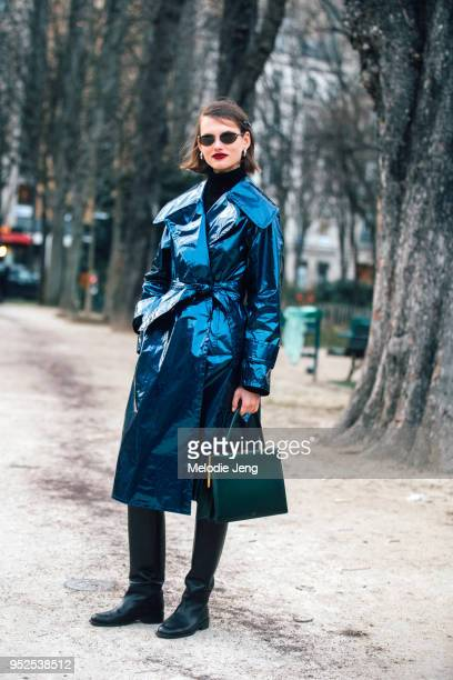 Model Giedre Dukauskaite wears frameless sunglasses a blue reflective trench coat a green Celine clasp rectangular handbag and long black boots after...