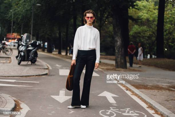 Model Giedre Dukauskaite wears pink Dior sunglasses a white to black pants brown fur bag and white shoes during Milan Fashion Week Spring/Summer 2019...