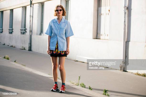 Model Giedre Dukauskaite wears triangular cateye sunglasses a a blue Prada buttonup shirt print skirt and red Salomon running sneakers after the Alyx...