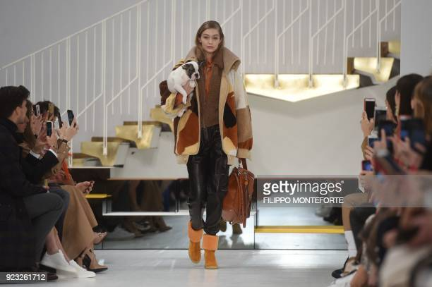 US model Gigi Hadid carrying a dog presents a creation by Tod's during the women's Fall/Winter 2018/2019 collection fashion show in Milan on February...