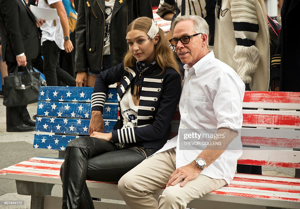Model Gigi Hadid sits with Designer Tommy Hilfiger before the fall 2016 collection show at New York Fashion Week in New York, September 9, 2016. / AFP / TREVOR