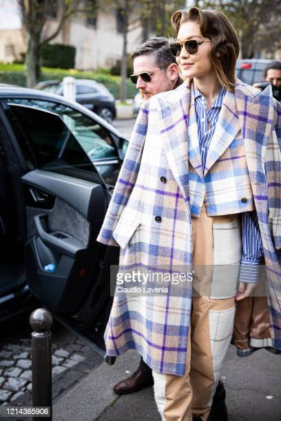 Model Gigi Hadid wearing a blue striped shirt blue and beige checked cropped blazer blue and cream checked coat and beige decorated pants is seen...