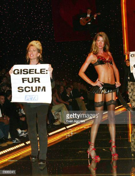 Model Gisele Bundchen walking the runway is interupted by antifur protestors at the 2002 Victoria's Secret Fashion Show at Lexington Avenue Armory in...