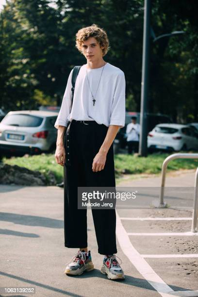 Model Giulio Donvito wears a white top a key necklace black pants and Balenciaga sneakers during Milan Fashion Week Spring/Summer 2019 on September...
