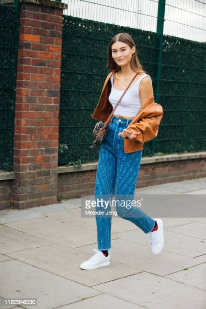 Model Grace Elizabeth wears a brown leather jacket off her shoulders, white tanktop, brown Burberry bag, blue jeans, and white Burberry sneakers...