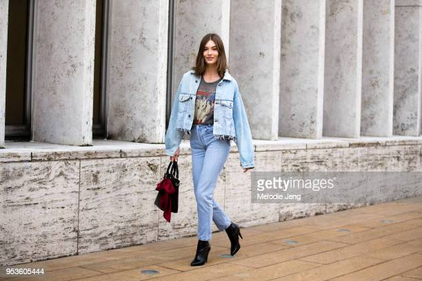 Model Grace Elizabeth wears a denim jacket and jeans with a graphic tshirt black purse and black heeled boots after the Michael Kors show at Lincoln...