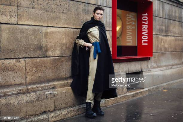 Model Grace Hartzel wears a long black cape over a cream jumpsuit with a blue belt and black lace up boots on March 04 2018 in Paris France