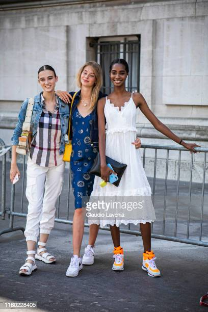 Model Greta Varlese , wearing a checked shirt, jeans jacket, white pants, Dior bag and white sandals, model Lauren de Graaf , wearing a blue printed...