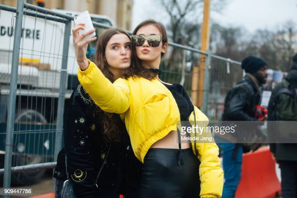 Model Greta Varlese wears reflective square sunglasses a yellow jacket and takes a selfie with a fan outside the Chanel show at Grand Palais on...