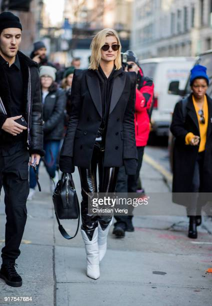 Model Hailey Baldwin wearing black blazer with strong shoulder line hoodie vinyl pants white boots black bag sunglasses seen outside Zadig Voltaire...