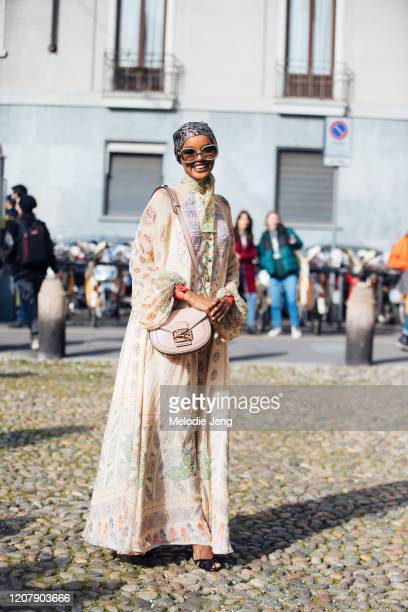 Model Halima Aden wears a floral headscarf overrsized sunglasses a pink Etro bagh and tan Etro print dress at the Etro show during Milan Fashion Week...