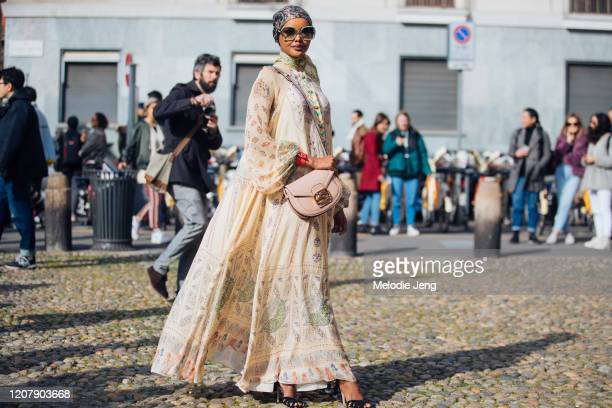 Model Halima Aden wears a floral headscarf oversized sunglasses a pink Etro bag and tan Etro print dress at the Etro show during Milan Fashion Week...