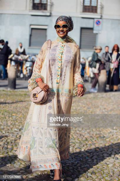 Model Halima Aden wears a floral headscarf oversized sunglasses a pink Etro Pegaso bag and tan Etro print dress at the Etro show during Milan Fashion...