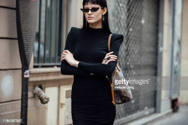 Model Hannah Elyse wears black cat-eye sunglasses, a black dress with pointed shoulders and a Louis Vuitton bag after the Olivier Theyskens show...