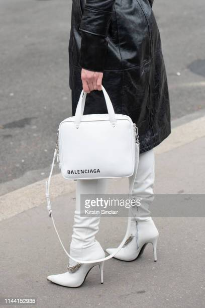 Model Hannah Ferguson wears a black leather trench coat, a white Balenciaga bag and white knee high heeled boots with silver chain detail on February...