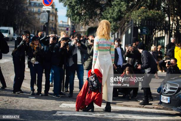 Model Hanne Gaby Odiele poses for a group of photographers and wears a rainbow top white pants red jacket and black bag after Miu Miu on March 6 2018...