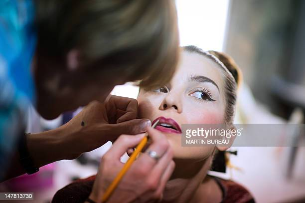 A model has her makeup done in the backstage of French designer Julien Fournie during the Haute Couture FallWinter 20122013 shows on July 3 2012 in...