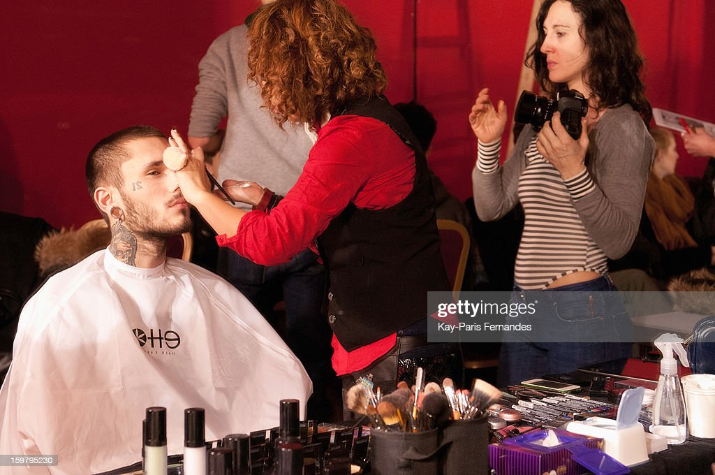 A model has his make-up done backstage before the Rynshu Men Autumn / Winter 2013 show as part of Paris Fashion Week on January 20, 2013 in Paris, France.