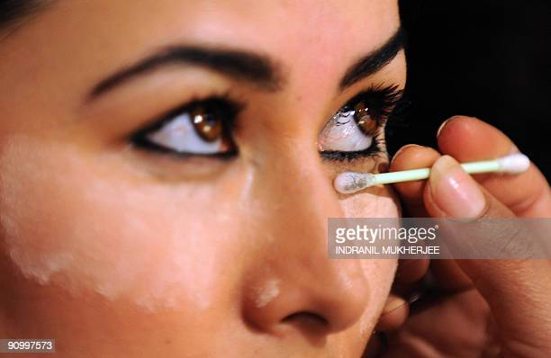 A model has makeup done backstage before the start of a show on the fourth day