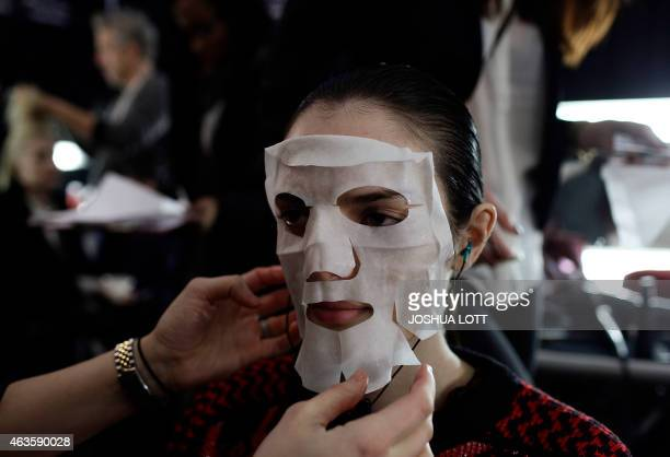 A model has moisturizer mask applied to her face backstage before presenting a creation by Carolina Herrera Fall/Winter collection during New York...