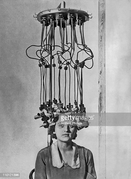 A model having her hair permed by a permanent wave machine at the Hairdressing Fair White City London 25th October 1928