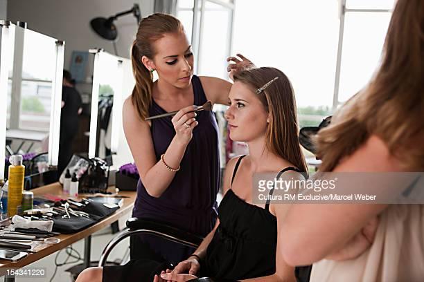 Model having her makeup done
