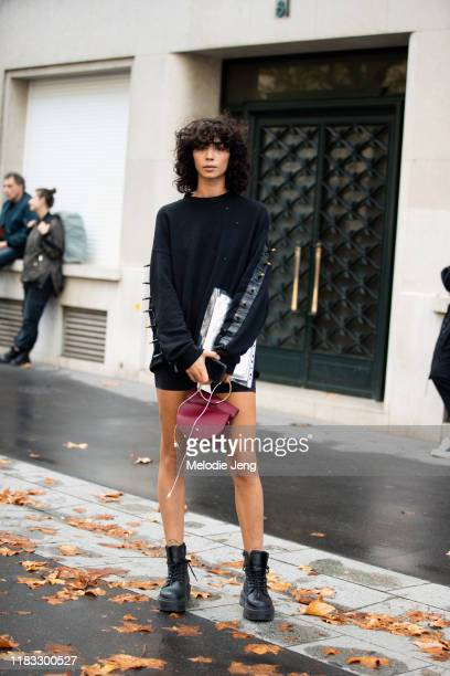 Model Hayat Ben Olohamed wears a black sweater with studs, red purse, and black combat boots after the Faith Connexion show during Paris Fashion Week...