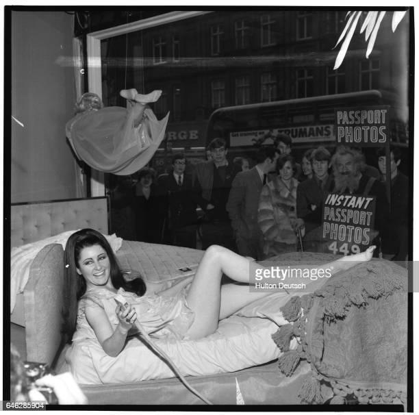 Model Hazel Whitfield demostrates a Sleepeezee bed in Selfridges' window on Oxford Street in London 1968