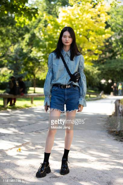 Model He Cong wears a green gingham shirt black Burberry crossbody bag black belt blue denim cutoff shorts black socks and black Prada boots after...