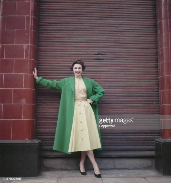 Model Heather Jeffrey wears a green coat over a yellow knee length dress in London April 1955