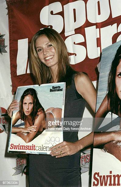 Model Heidi Klum holds the new Sports Illustrated swimsuit calendar at the Fashion Cafe That's Klum on the cover