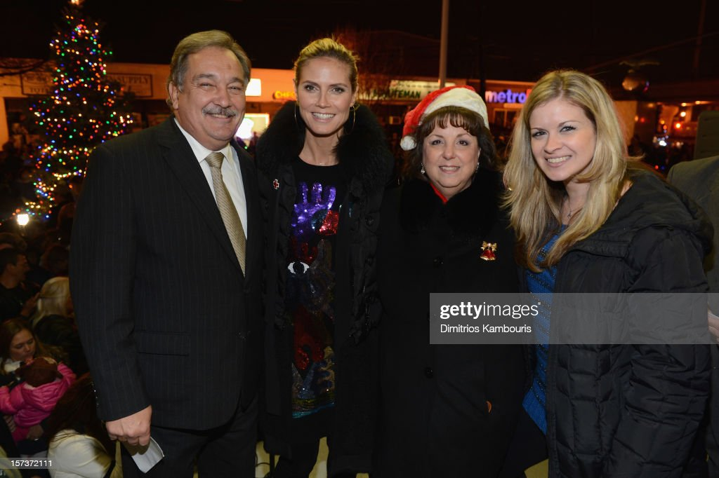 Model Heidi Klum (2nd L)) poses for a photograph with Village of Lindenhurst Mayor Thomas A. Brennan (L) and his family during a tree lighting ceremony as they team up with friends at AOL, Patch and The American Red Cross to benefit Hurricane Sandy relief efforts at American Red Cross and Patch Sites on December 2, 2012 in Lindenhurst, New York.
