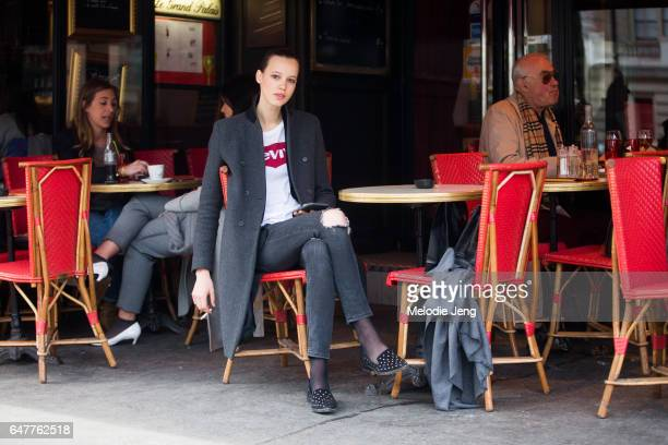 Model Heloise Giraud wears a Levi's tshirt and sits at a cafe outside the Vanessa Seward show on March 3 2017 in Paris France