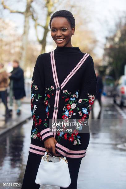 Model Herieth Paul wears the goldflake eye makeup from the Akris show and a black cardigan with floral knit and a white Elleme bag on March 04 2018...