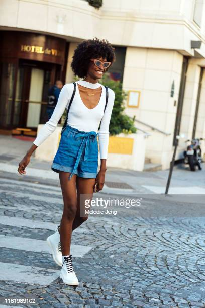 Model Hilary Cerezo wears a pink sunglasses, a white top, denim shorts, and white boots after the Zuhair Murad show during Couture Fashion Week...