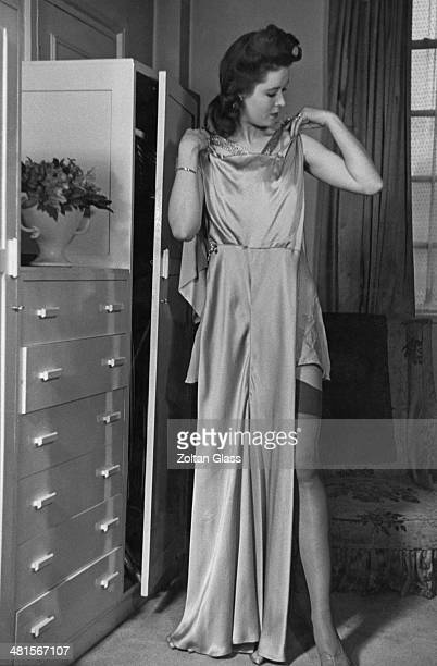 A model holding a white satin evening dress which is going to be cut up to make a blouse July 1941 From an article in Picture Post magazine advising...