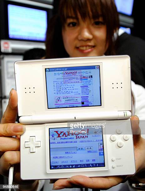Model holds a Nintendo DS Lite handheld game console displaying the Yahoo! Japan search engine Web page following a press briefing in Tokyo...