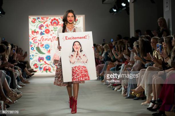 A model holds a poster with the picture of Designer Lena Hoschek at the end of Lena Hoschek fashion show during the MercedesBenz Berlin Fashion Week...